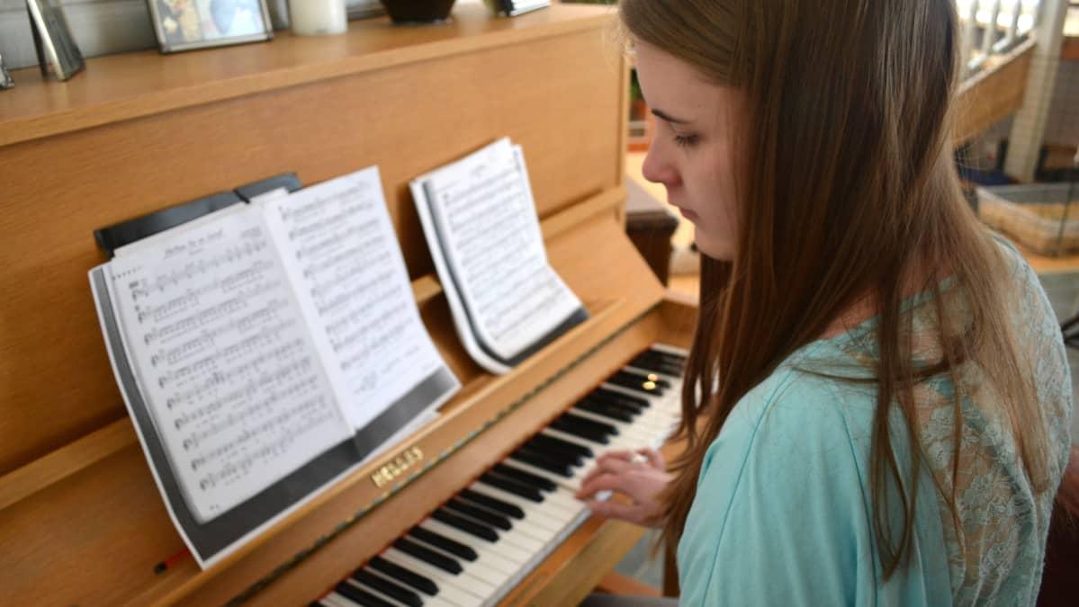 Vera Koponen soittaa kotonaan pianoa.