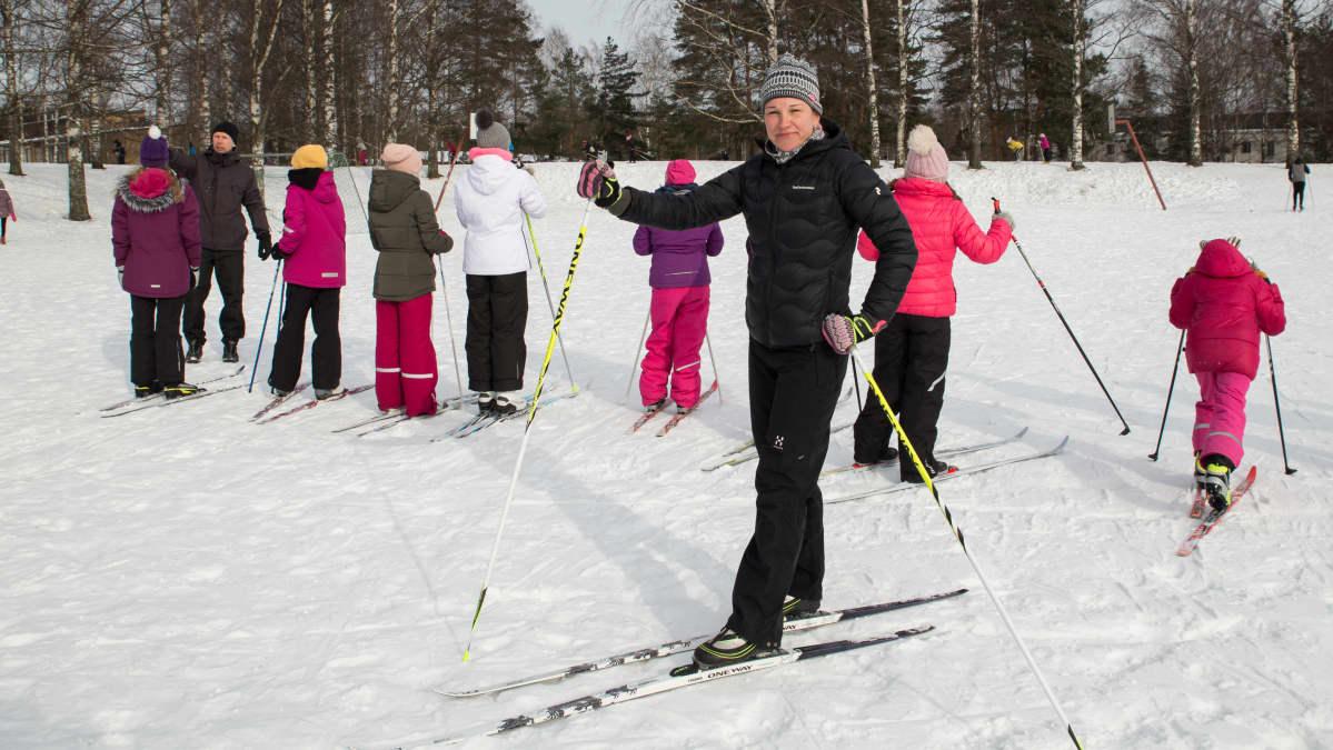 Opettaja ja koululaisia hiihtämässä