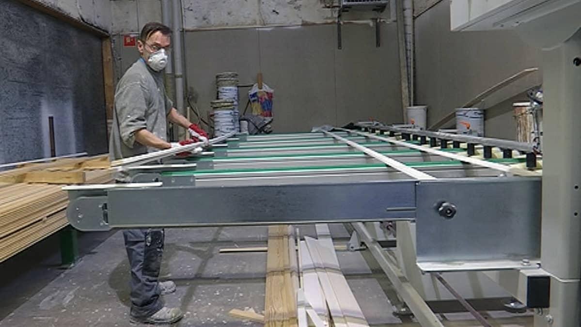 Mies työssä puupaneelien maalauskoneella