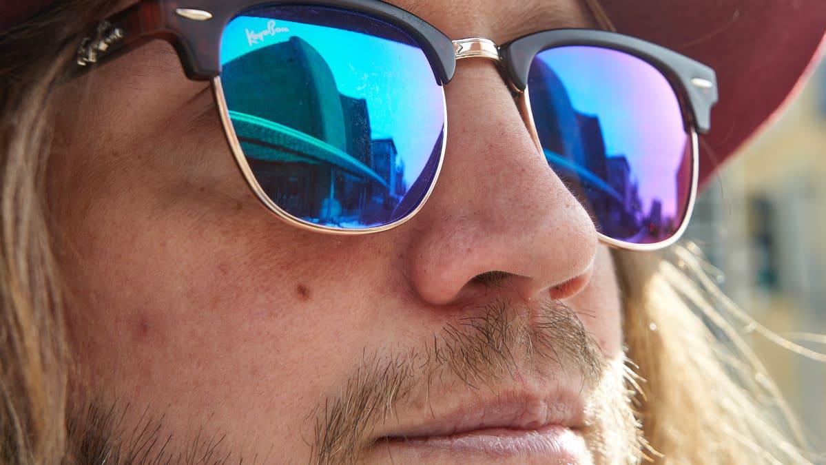 Juha Dallas aurinkolaseineen. Heijastuu kulttuuritalo.