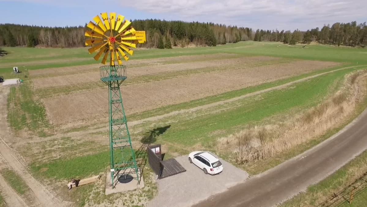 pieni tuulimylly kuvattuna ilmasta ja peltomaisema