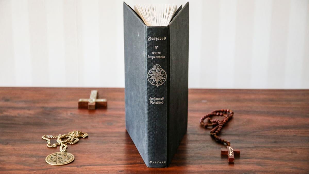 Azazelin tähden jäsenriipus, Fosforos-kirja, krusifiksi ja ristiriipus pöydällä.
