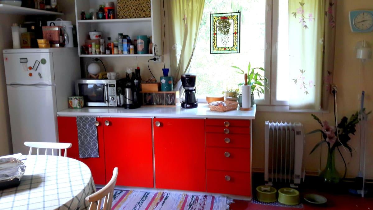 Punaiset keittiön kaapit ja pinnatuoleja