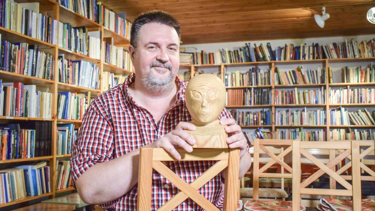 Marko Kananen istuu puisen humanoidipatsaan kanssa kirjahyllyn edessä.