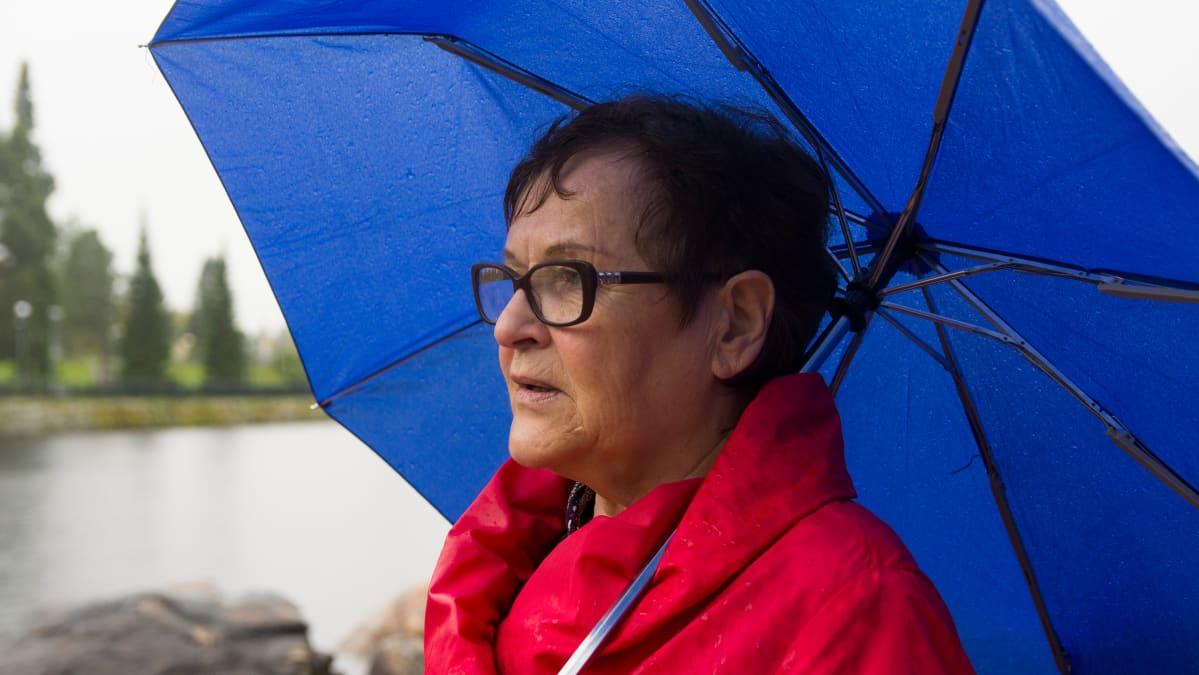 Nainen seisoo joen rannassa sateenvarjon alla.
