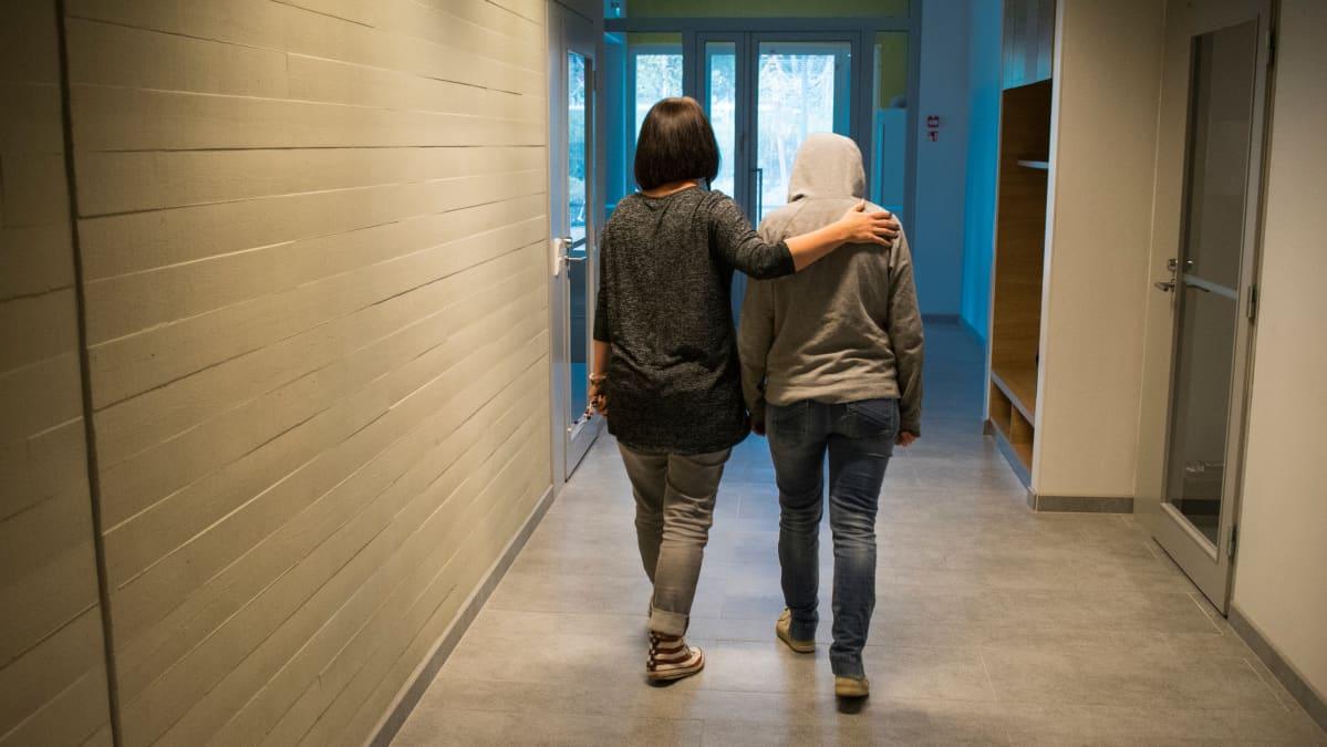 Huppariin pukeutunut nuori kävelee koulun käytävällä pää painuksissa, opettaja kulkee rinnalla käsi nuoren olkapäällä
