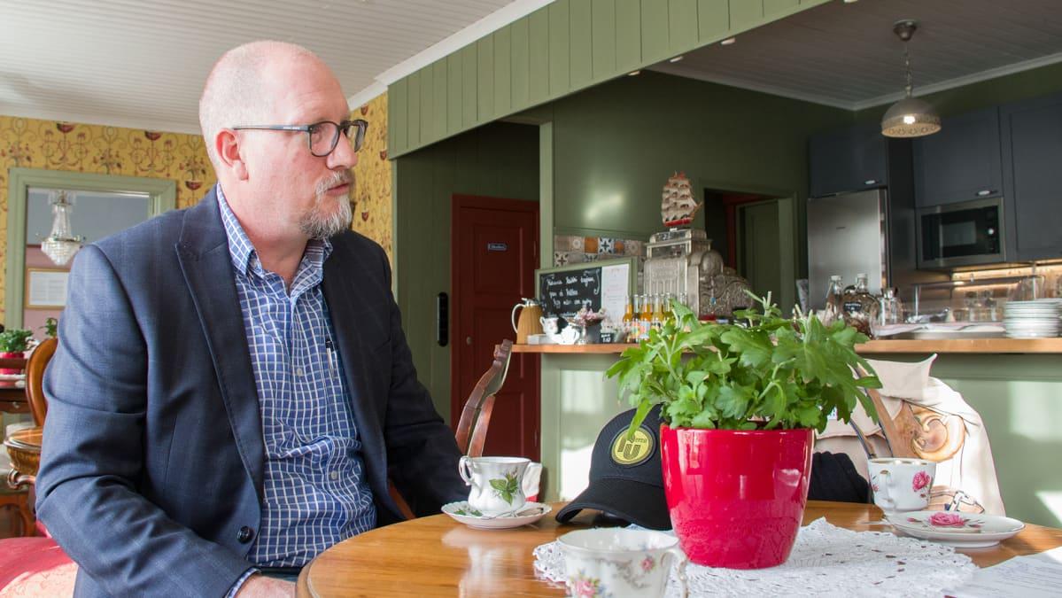 Raahen kultakaivoksen johtaja Joe Ranford istuu kahvilassa pöydän ääressä.