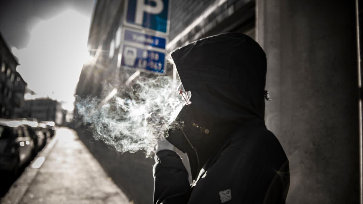 Ihminen polttaa kannabista tai tupakkaa kadulla