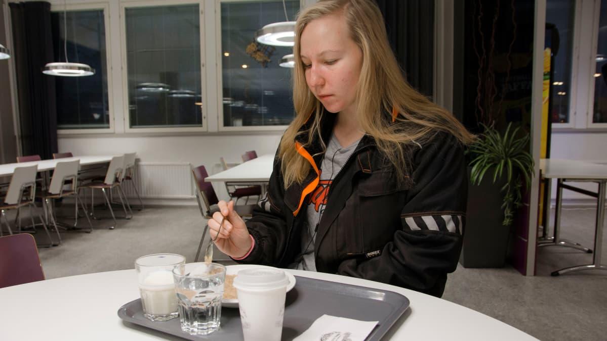 Opiskelija syö ruokalassa aamupuuroa.