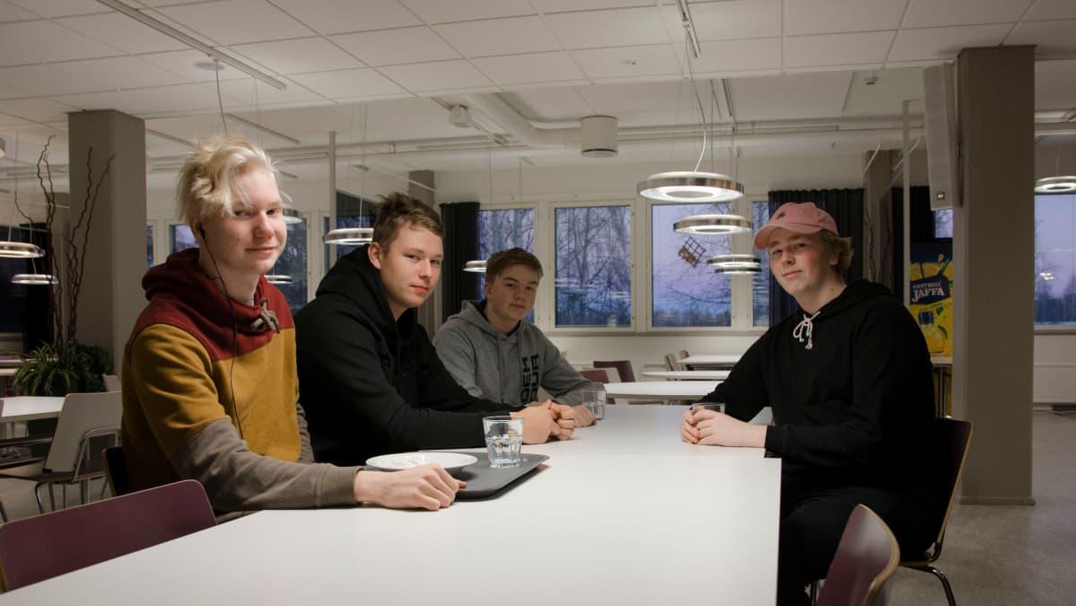 Opiskelijoita istuu pöydän ääressä koulun ruokalassa.