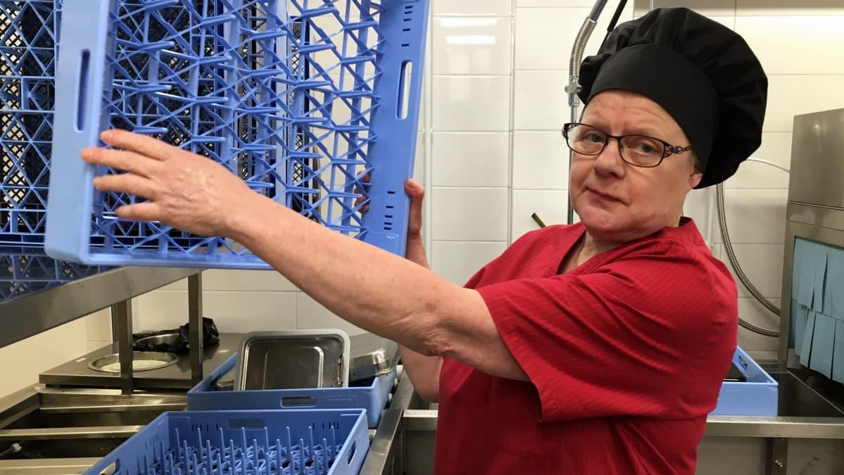 Ruokapalvelutyöntekijä Seija Karttunen pesee astioita Kontioniemen koulun keittiössä.