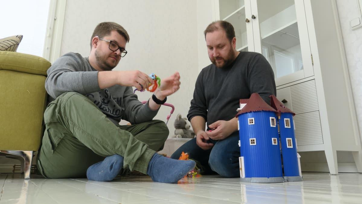 Kaksi miestä lasten lelujen keskellä