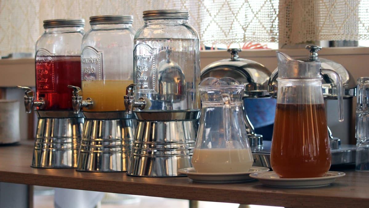 Mehu- ja vesisäiliöitä aamupalapöydässä.