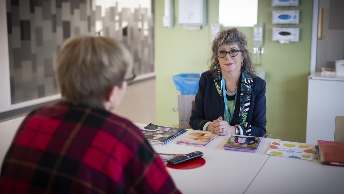 Nainen keskustelee toiselle sairaalatiloissa.