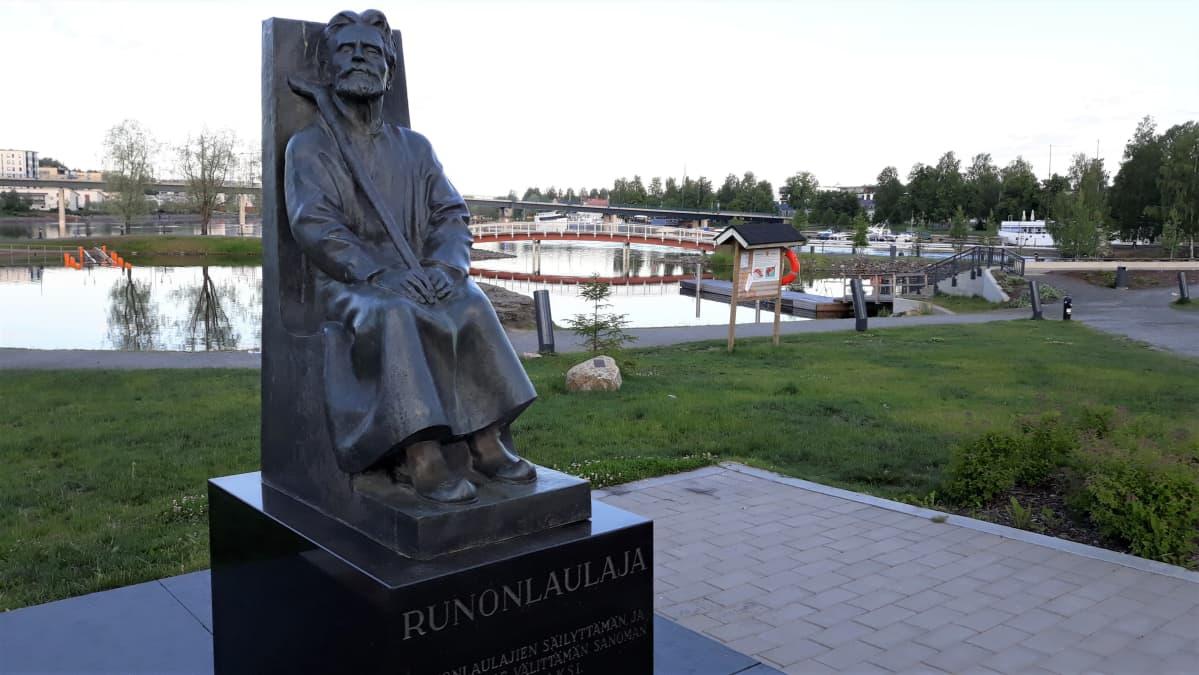 Runonlaulaja Miihkali Arhippaisen patsas muistuttaa runonlaulajien merkityksestä Joensuun Ilosaaressa.