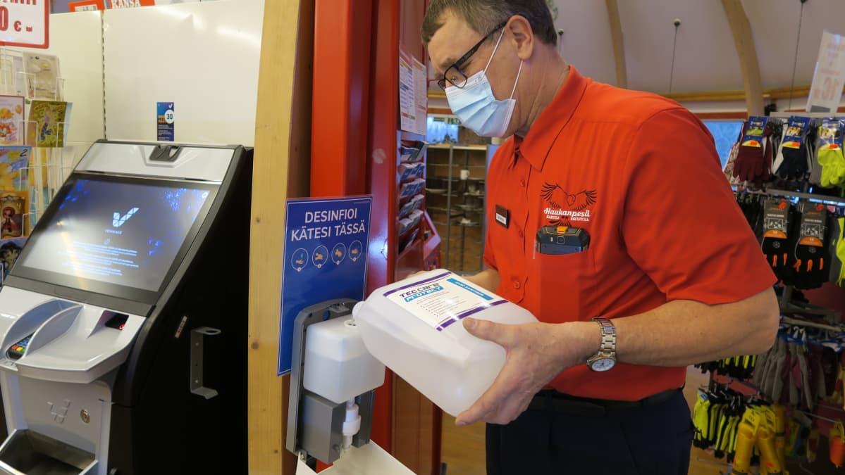 Ykköspesän yrittäjä Ahti Norja täyttää käsidesiautomaattia. - Asiakkaat kyllä käyttävät tätä todella innokkaasti, ei oikeastaan kukaan kävele ohi tullessa eikä lähtiessä, hän kiittää.