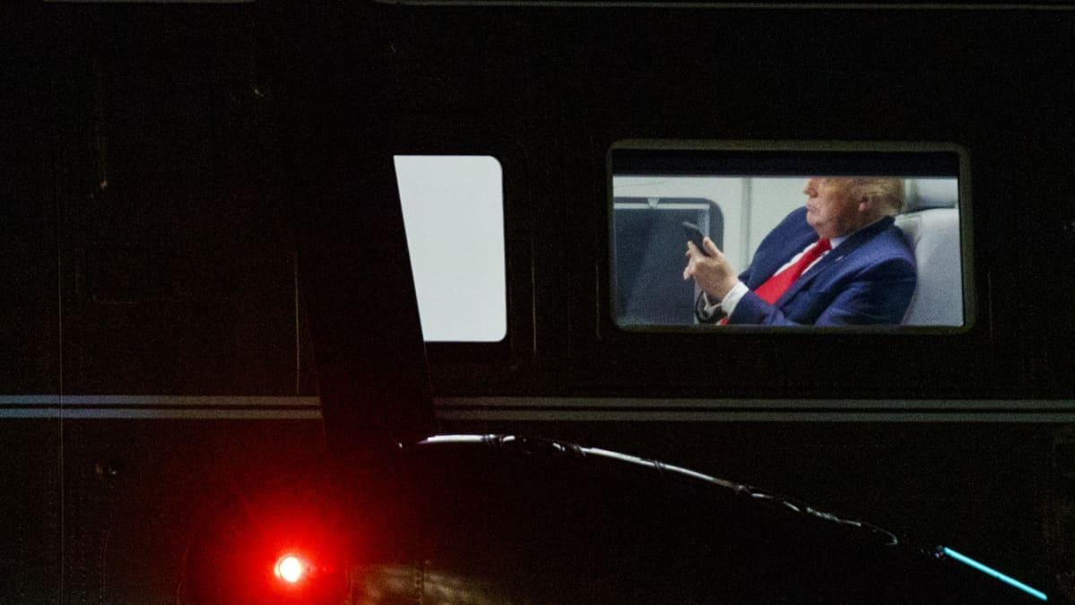 Donald Trump katsoo puhelintaan.