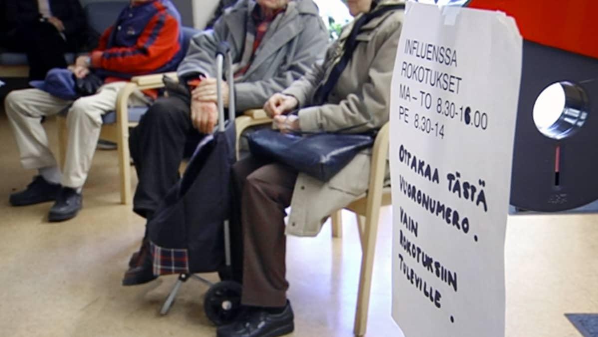 Ihmiset jonottavat vastaanotolle terveyskeskuksessa.
