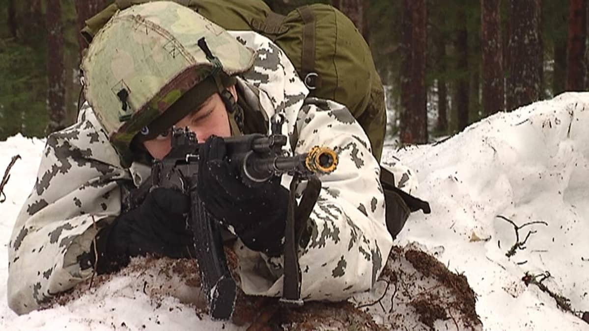 Varusmies tähtää rynnäkkökiväärillä maastossa.