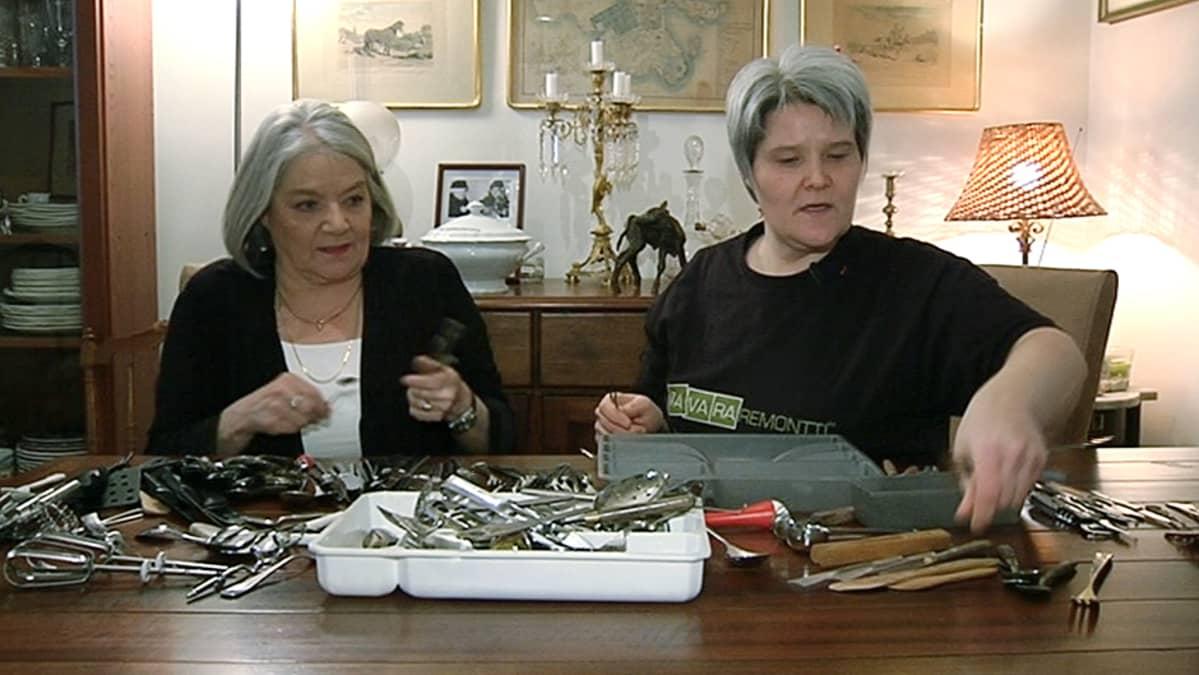 Kaksi naista lajittelemassa ruokailuvälineitä.