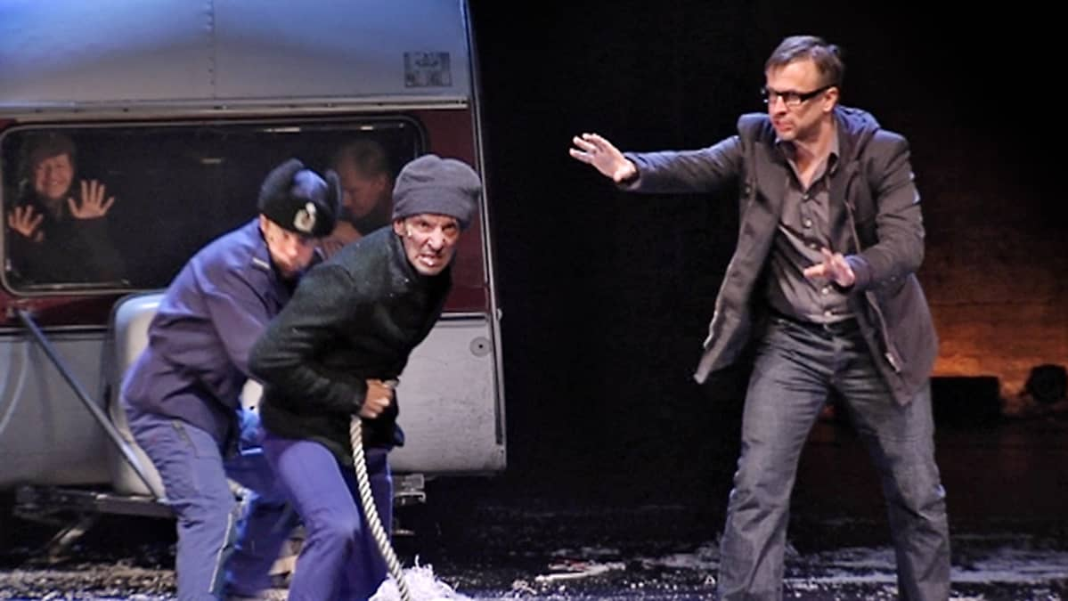 Kaksi miestä vetää köydellä suu vaahdossa asuntovaunua. Heidän oikealla puolellaan, pikkutakkiin pukeutunut mies yrittää rauhoitella heitä.