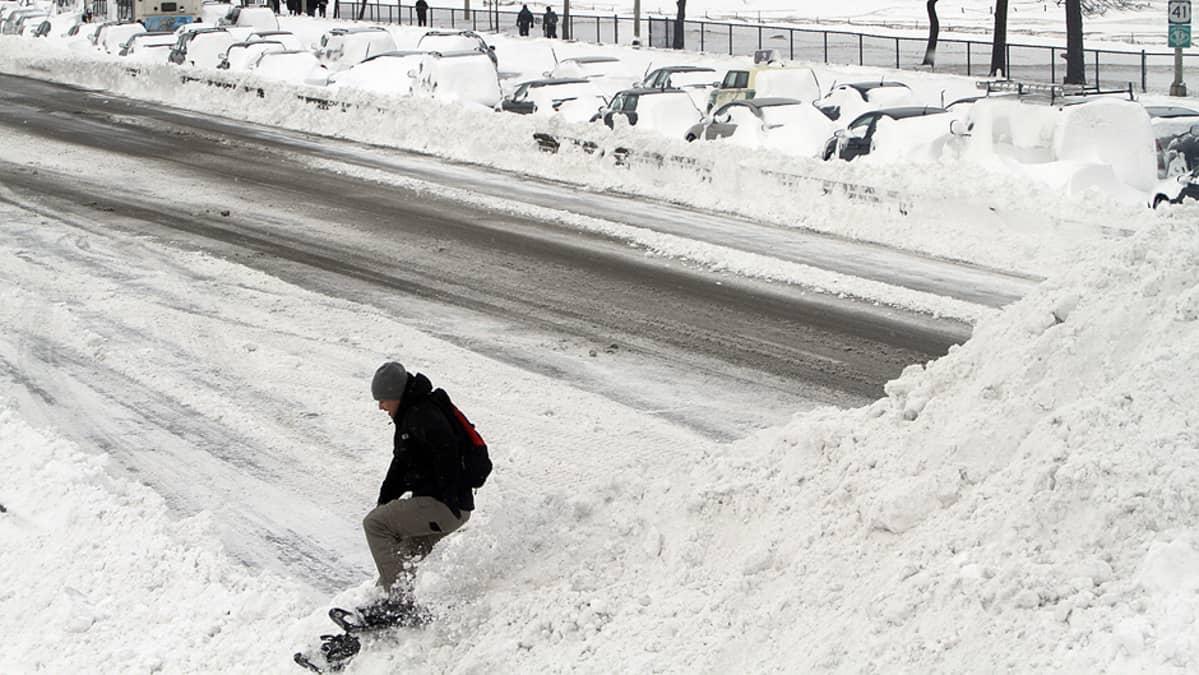 Poika lumilautailee tieltä auratulla lumikasalla.