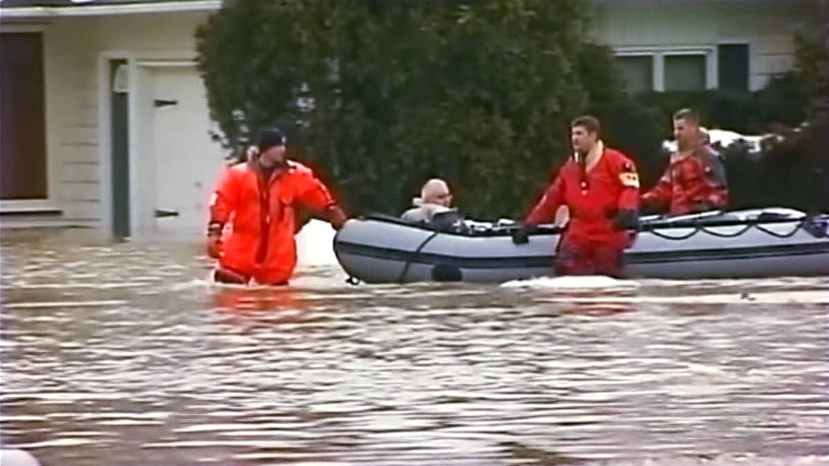 Palomiehet kahlaavat tulvavedessä vetäen kumivenettä.