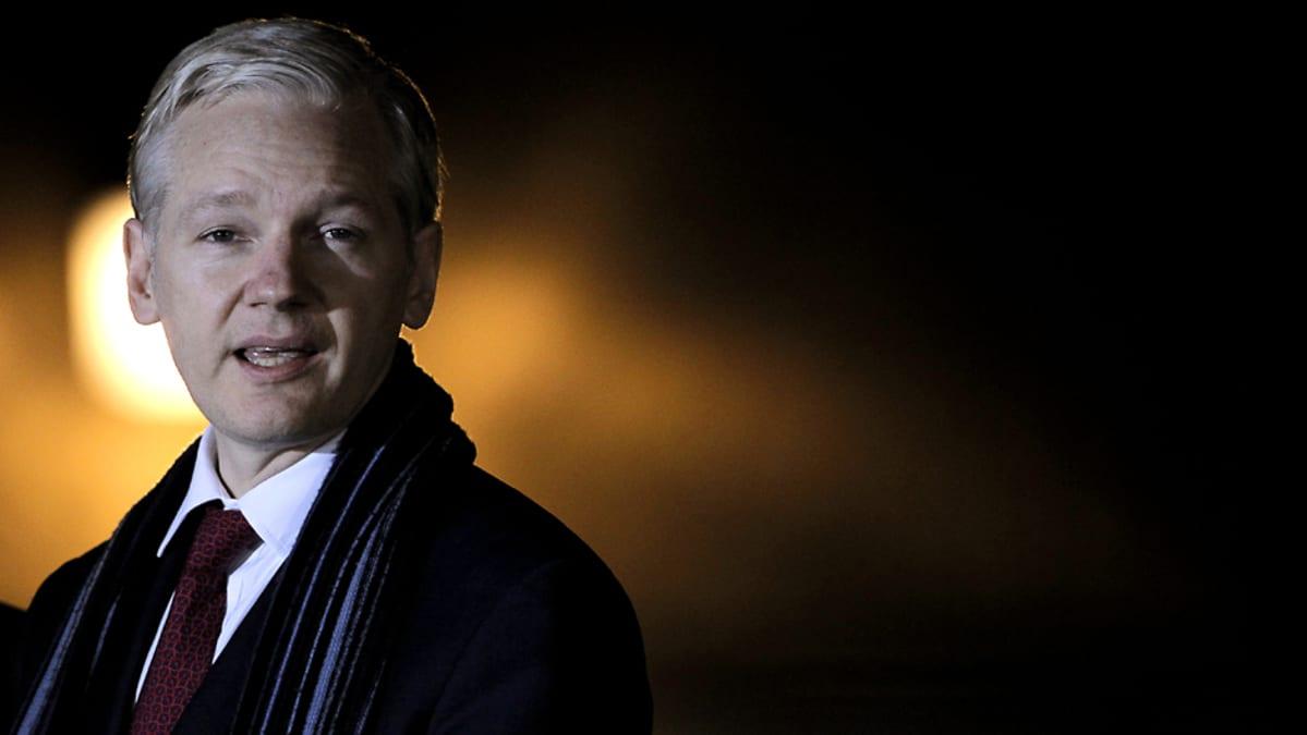 Julian Assange kuvattuna yöllä dramaattinen takavalo takanaan.