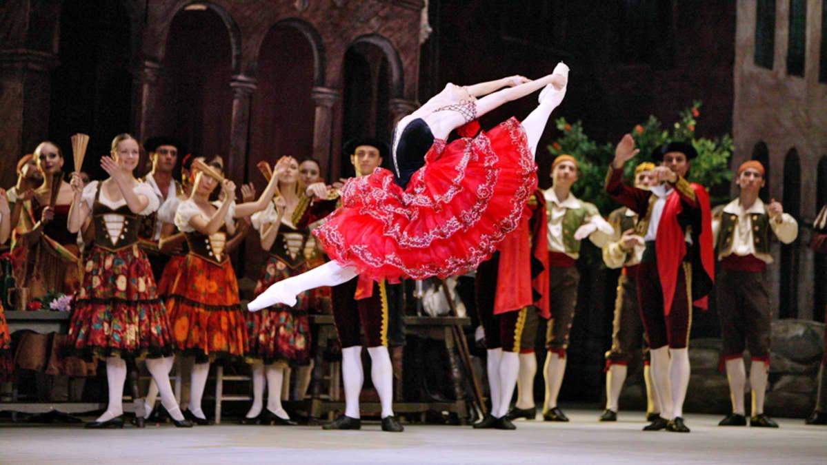 Balettitanssija korkealla ilmassa, säestäjäryhmän edessä, hienossa punaisessa mekossaan.