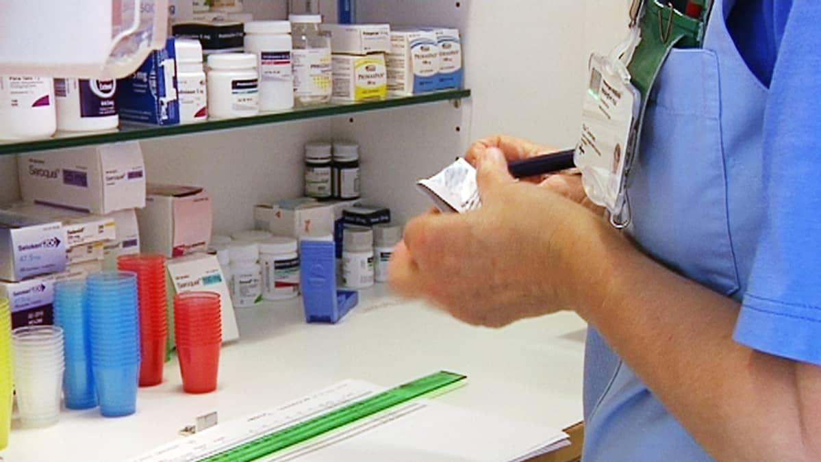 Sairaanhoitaja käsittelee reseptiä lääkekaapilla.