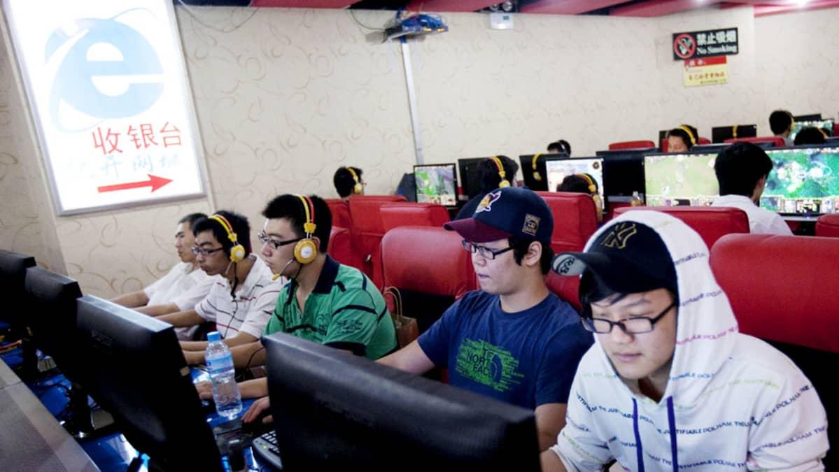 Nuoret miehet istuvat tietokoneiden ääressä kiinalaisessa nettikahvilassa Pekingissä.