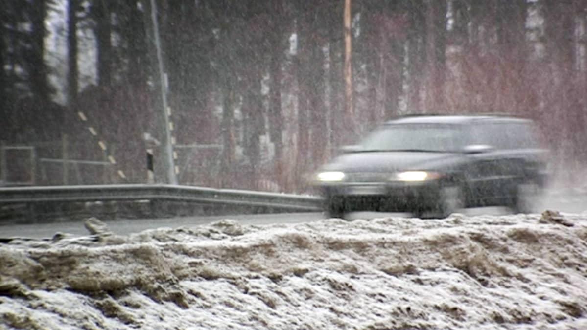 Auto liikenteessä räntäsateessa.