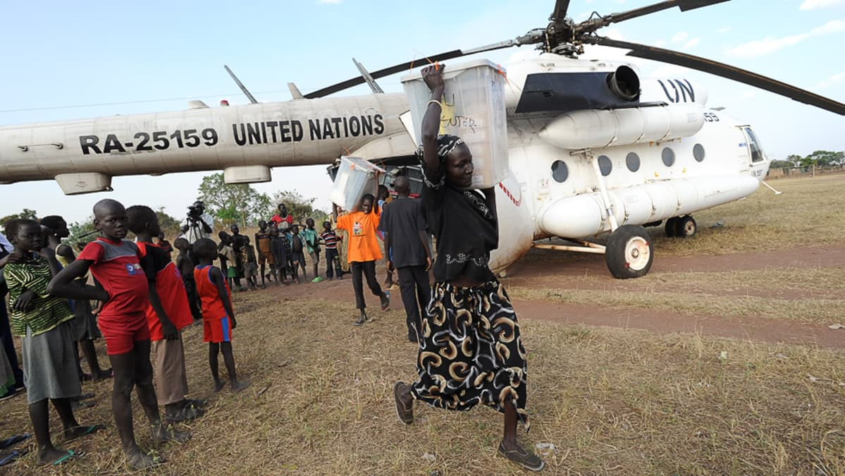 Vaaliuurnia kannetaan YK:n helikopterista Talissa, eteläisessä Sudanissa.