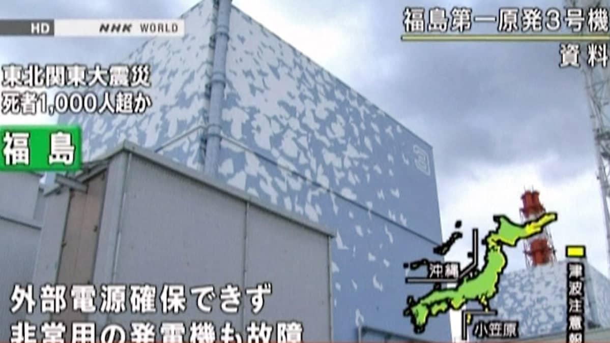 Fukushiman kolmosreaktori kuvattuna ulkoa, alakulmasta ylöspäin. Tummia pilviä taivaalla, Japanin tv:n tekstiä ja grafiikkaa kuvan päällä.