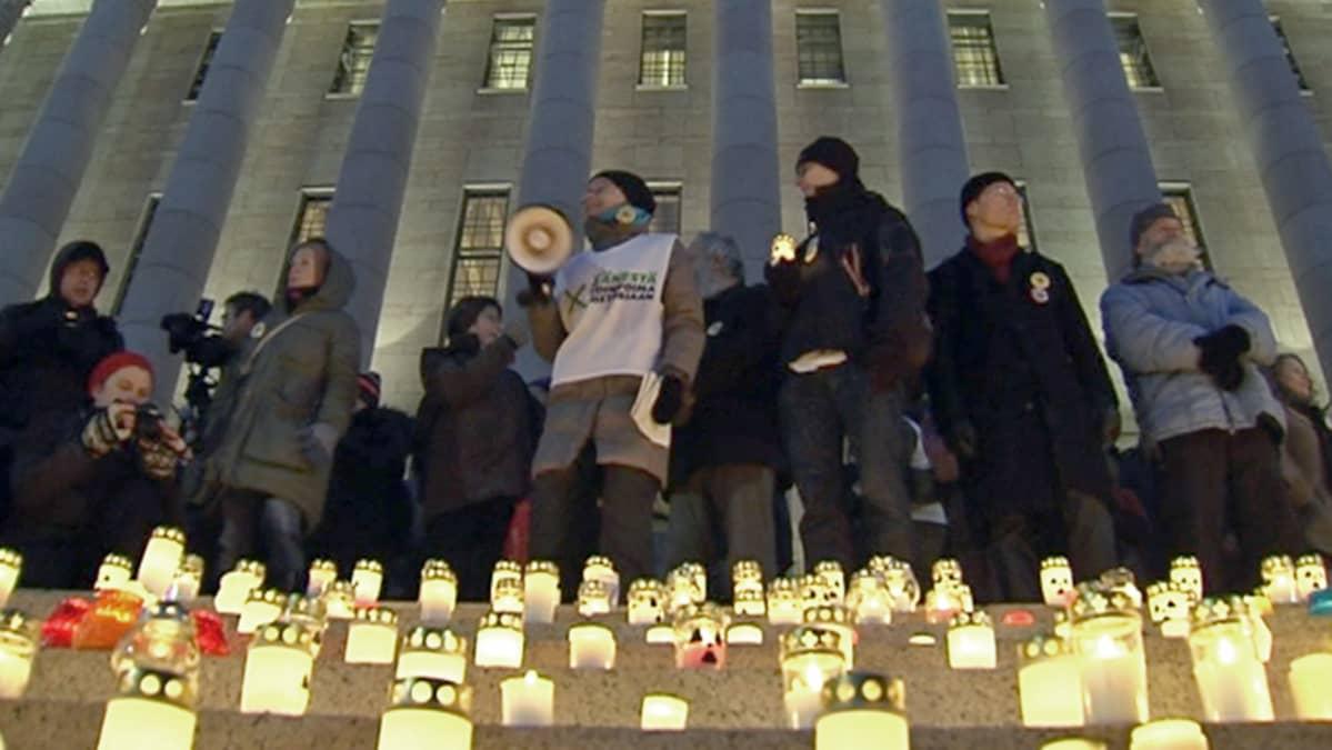 Ihmisiä eduskuntatalon rappusilla kynttilärivistön takana