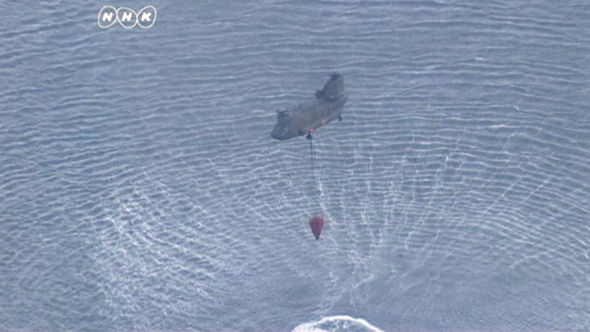 Helikopteri nostaa vettä merestä Fukushiman ydinvoimalan edustalla.