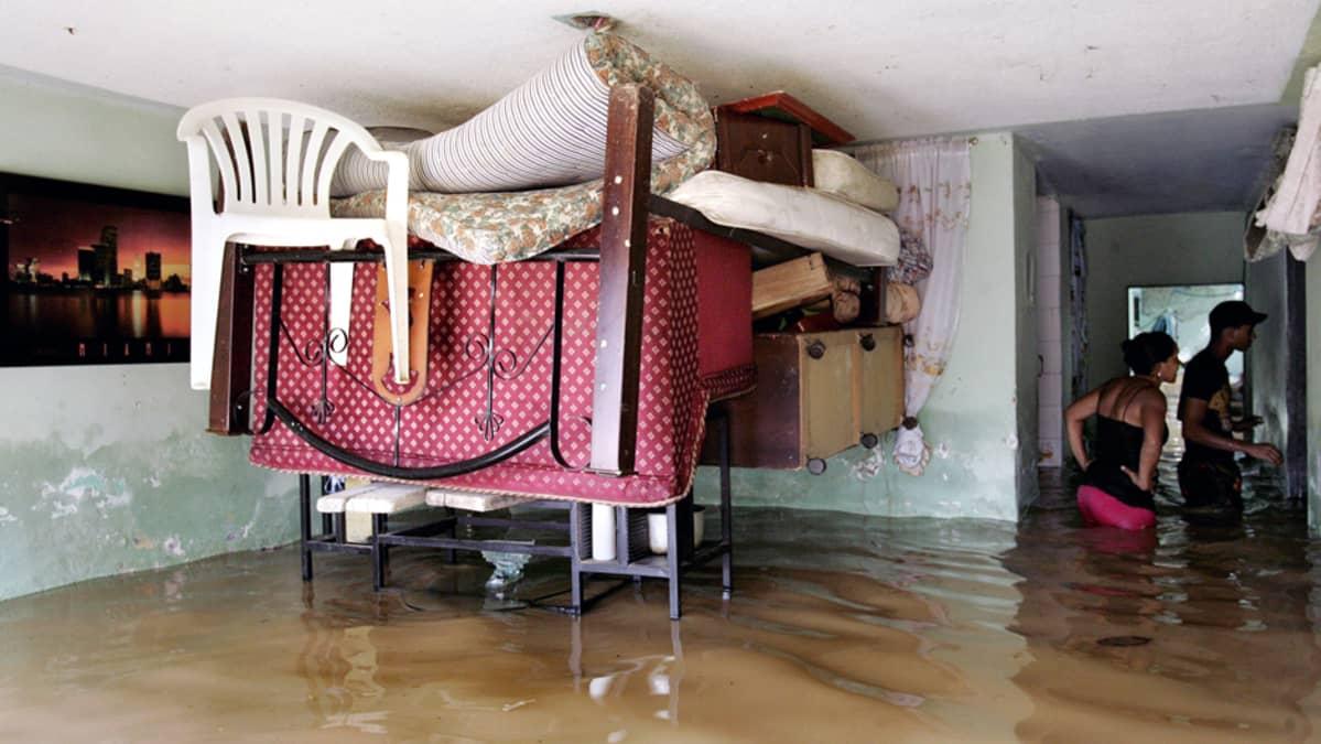 Kolumbialainen perhe yrittää pitää tavaroitaan kuivana tulvaveden valtaamassa kodissaan .