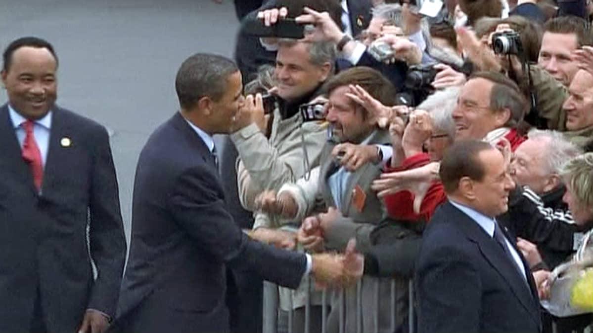 Yhdysvaltain presidentti Barack Obama ja Italian pääministeri Silvio Berlusconi tervehtivät G8-kokousta seuraamaan tulleita ihmisiä.
