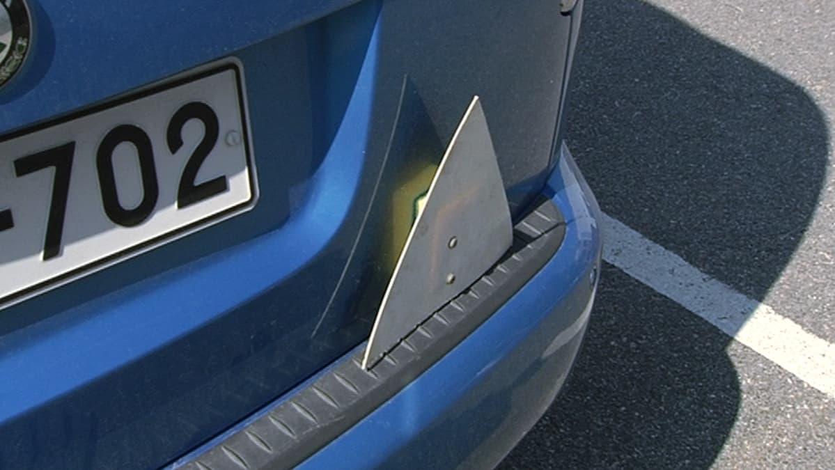 Opetuskolmio auton takapuskurissa.