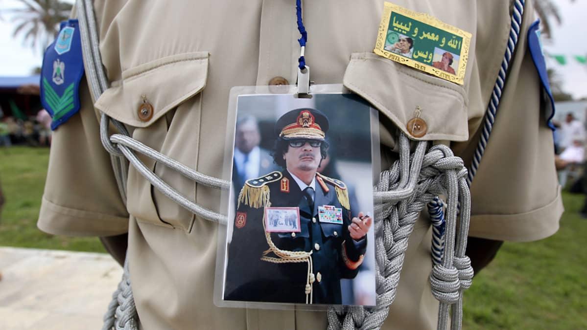 Libyalainen sotilas kantaa paitansa etupuolella laminoitua Gaddafin kuvaa.