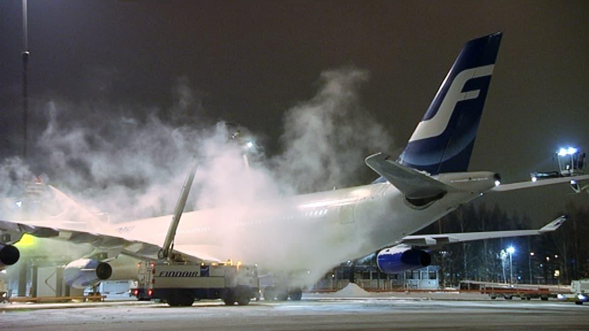 Lentokoneen siivistä poistetaan jäätä.