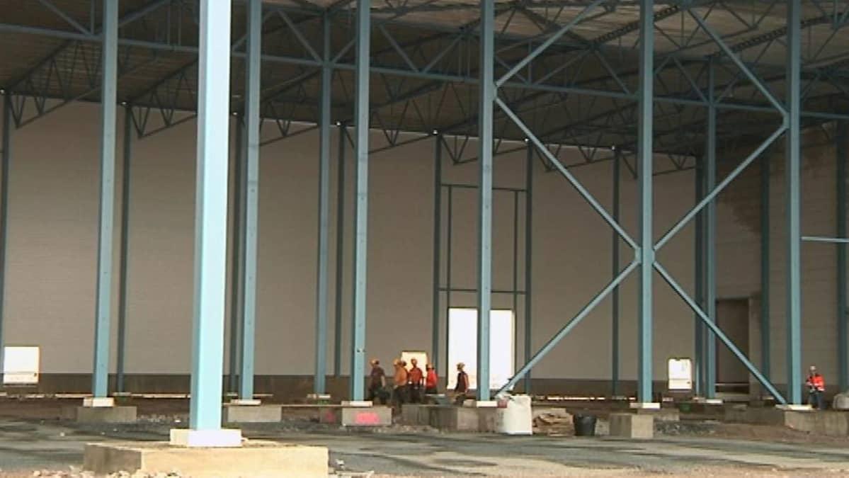 Rakennusmiehiä suuressa tehdashallissa
