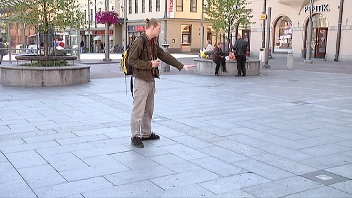 Taiteilija Juho Viitala esittelee Keskustorilla kohtaa johon katumaalaus oli tarkoitus tehdä.