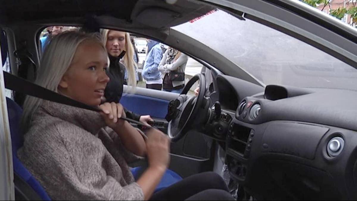 Tyttö laittaa autossa turvavyötä.