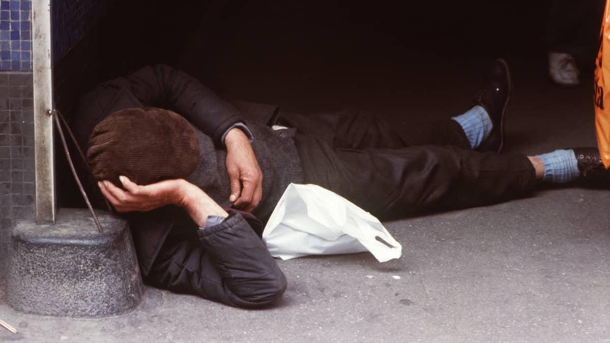 Päihtynyt mies nukkuu kadulla.
