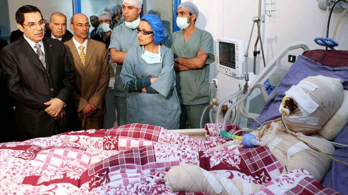 Tunisian presidentti Zine El-Abidine Ben Ali vierailee itsensä tuleen sytyttäneen Mohamed Bouazizin sairaalahuoneessa.