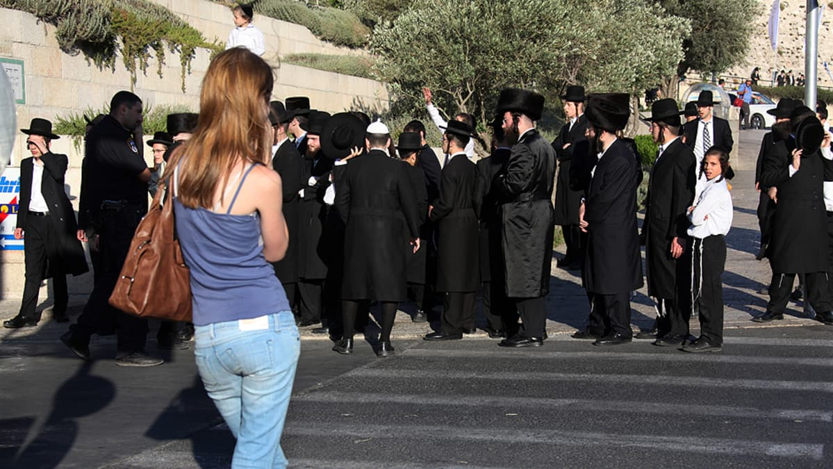 Nuori nainen ja joukko ortodoksijuutalaisia.