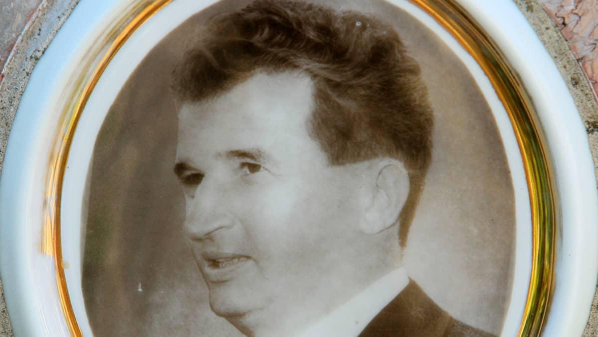 Hautakiveen kiinnitetty potretti Nicolae Ceausescusta.