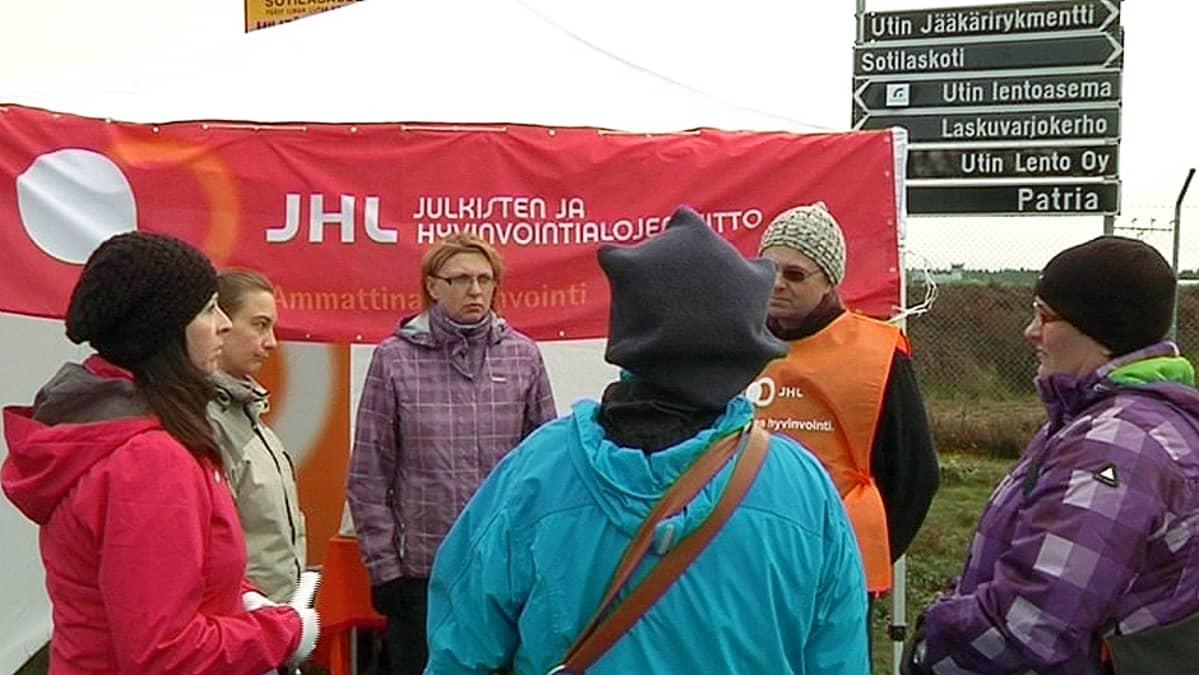 Julkisten ja hyvinvointialojen liittoon kuuluvia Utin jääkärirykmentin keittiöhenkilökunnan jäseniä osoittamassa mieltään jääkärirykmentin kasarmin porttien ulkopuolella lokakuun lopulla.