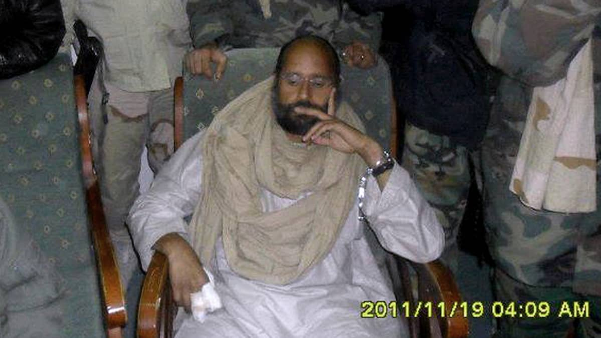 Saif al-Islam hänet pidättäneiden väliaikaishallinnon joukkojen ympäröimänä.
